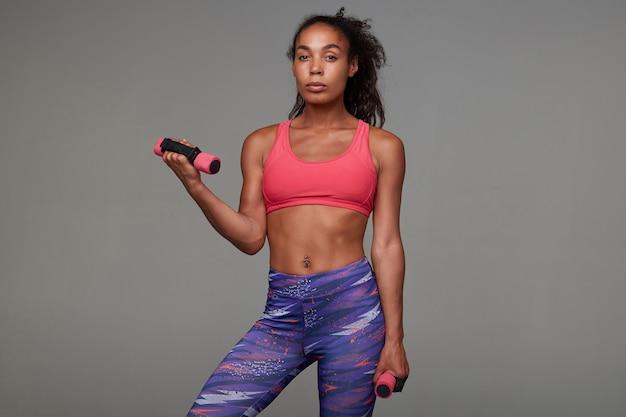 Atrakcyjna młoda sportowa, kręcona brunetka kobieta o ciemnej skórze, o dobrym ciele, każdego ranka uprawia sport, trzymając hantle w rękach podczas pozowania