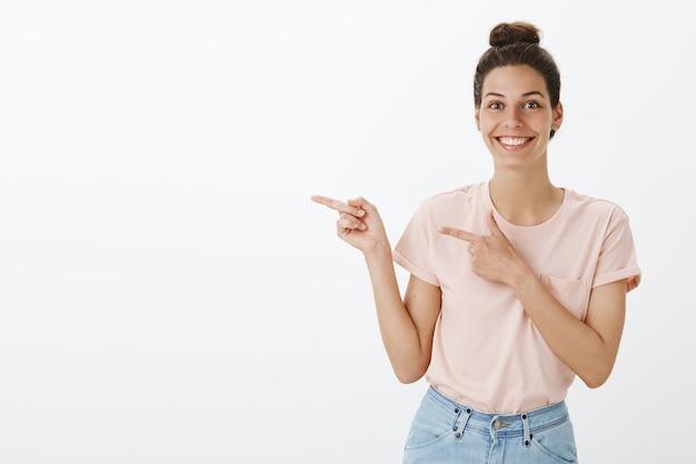 Atrakcyjna młoda stylowa kobieta pozuje na białej ścianie