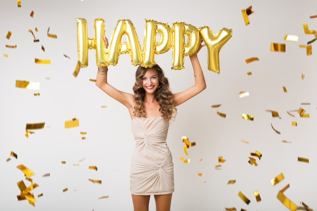 Atrakcyjna młoda stylowa kobieta świętuje nowy rok, trzymając balony szczęśliwe litery, latające złote konfetti, uśmiechnięta szczęśliwa, odizolowana, ubrana w sukienkę