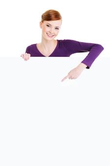 Atrakcyjna młoda uśmiechnięta kobieta patrząc na kamery i wskazuje na pusty plakat