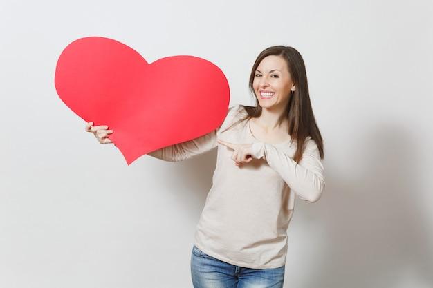 Atrakcyjna młoda uśmiechnięta kobieta wskazując duże czerwone serce w rękach na białym tle. skopiuj miejsce na reklamę. z miejscem na tekst. dzień świętego walentego lub koncepcja międzynarodowy dzień kobiet.