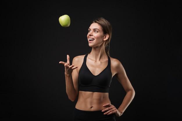 Atrakcyjna młoda zdrowa kobieta fitness ubrana w sportowy stanik i szorty na białym tle na czarnym tle, łapiąca zielone jabłko