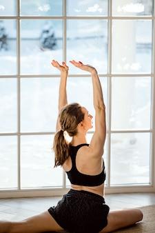 Atrakcyjna młoda zdrowa kobieta w sportowy czarny top i legginsy robi joga, rozciąganie w domu