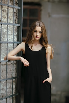 Atrakcyjna moda kobieta w czarnej sukience pozuje w pobliżu białej ściany
