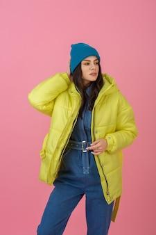 Atrakcyjna modelka aktywnej kobiety pozuje na różowej ścianie w kolorowej zimowej kurtce puchowej w jasnożółtym kolorze, trend w modzie na ciepły płaszcz