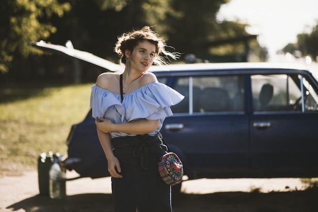 Atrakcyjna modelka w sukience z odkrytymi ramionami, która pozuje w pobliżu pojazdu