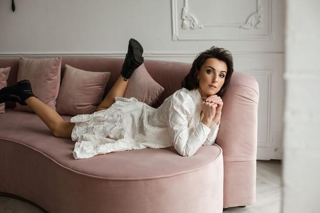 Atrakcyjna modna dama w czarnych butach z białą sukienką leży na różowej sofie i wygląda zamyślona. koncepcja stylu i mody