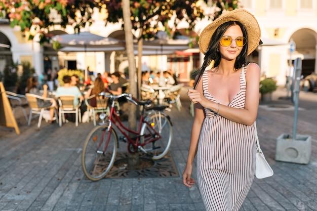 Atrakcyjna modna dziewczyna w żółte okulary pozuje z uśmiechem przed rowerem