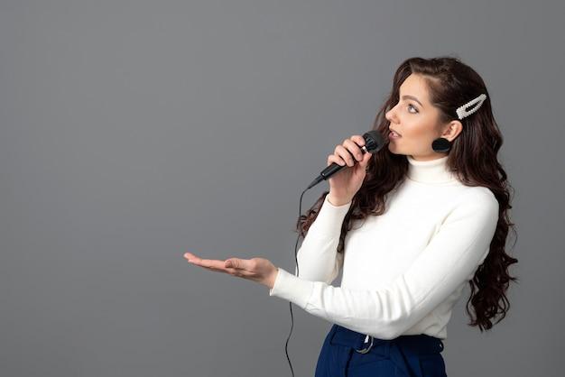 Atrakcyjna mówczyni konferencyjna podczas prezentacji, trzyma mikrofon i wykonuje pewne gesty, na szarym tle