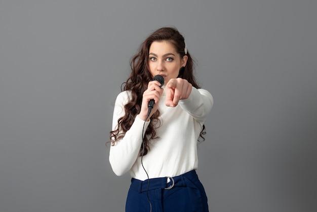 Atrakcyjna mówczyni konferencyjna podczas prezentacji, trzyma mikrofon i wykonuje pewne gesty, odizolowane na szaro
