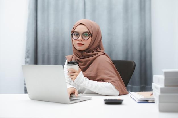 Atrakcyjna muzułmańska biznes kobieta ręka trzyma filiżankę kawy podczas pracy w domowym biurze.