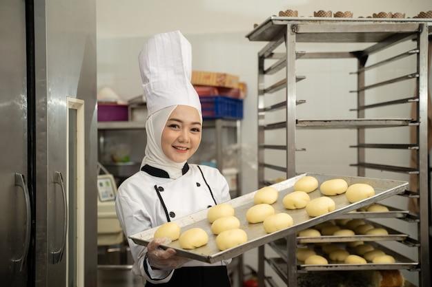 Atrakcyjna muzułmańska kobieta zawód szefa kuchni trzymając tacę, uśmiechając się do aparatu nosić hidżab