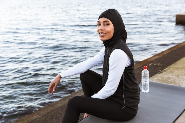 Atrakcyjna muzułmańska sportsmenka nosząca hidżab na zewnątrz, siedząca na macie fitness