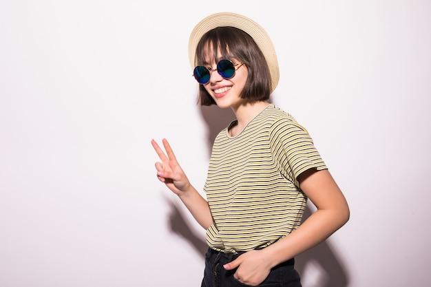 Atrakcyjna nastolatka hipster w kapeluszu, okulary na białym tle