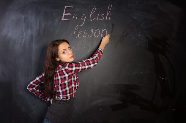 Atrakcyjna nauczycielka daje lekcję angielskiego, pisząc na czarnej tablicy klasowej i odwracając się z poważnym wyrazem twarzy w kierunku kamery