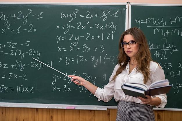 Atrakcyjna nauczycielka w okularach w pobliżu tablicy z obliczeń matematycznych. powrót do szkoły