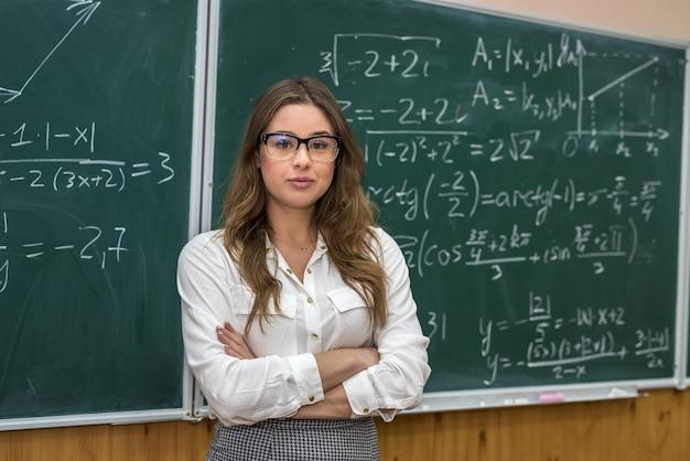 Atrakcyjna nauczycielka w okularach w pobliżu tablicy z obliczeniami matematycznymi.