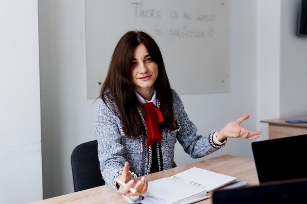 Atrakcyjna nauczycielka wyjaśnia zasady w klasie języka angielskiego. edukacja na uniwersytecie. prywatna nauka w zagranicznej szkole z uczennicą. nauczyciel wyjaśnia gramatykę języka ojczystego na laptopie.
