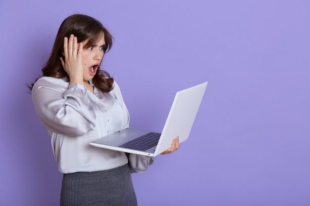 Atrakcyjna nerwowa młoda biznesowa kobieta z laptopem w rękach, patrząc na ekran urządzenia z zszokowaną miną, dotykając ręką głowy, trzyma szeroko otwarte usta, stoi przed liliową ścianą.