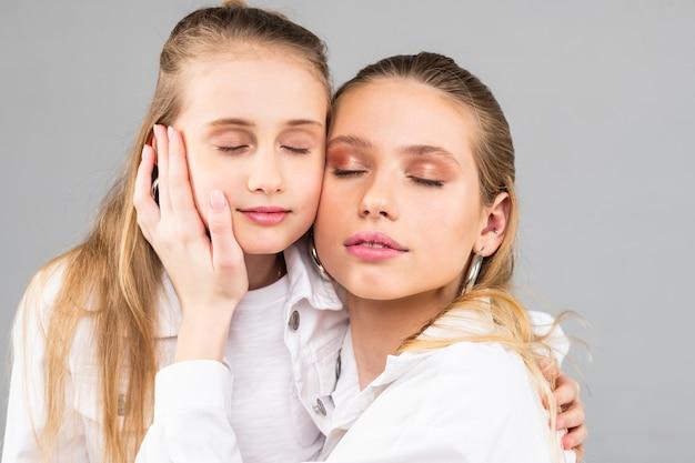 Atrakcyjna nieskazitelna kobieta łącząca twarze ze swoją małą, długowłosą siostrą, stojąc na szarym tle