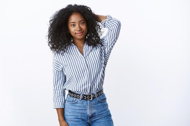 Atrakcyjna, nieśmiała, delikatna afroamerykanka, kędzierzawa pracownica trzymająca rękę za głową niepewna, niepewna, uśmiechnięta, przyjacielska, niezręczna, niewygodna nowi ludzie wokół, biała ściana