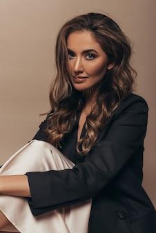 Atrakcyjna nieśmiała dziewczyna siedzi samotnie i trzyma się na kolanach. nagi, stylowy makijaż i długie kręcone fryzury. na ciele czarna kurtka i kremowa sukienka.