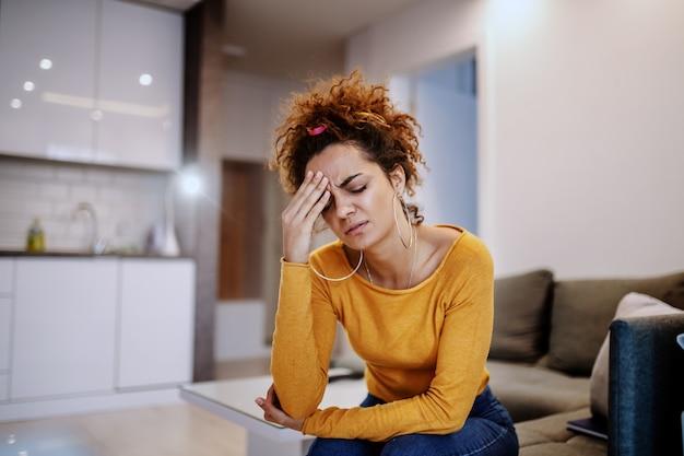 Atrakcyjna opalona brunetka kaukaski z kręconymi włosami siedzi na kanapie w salonie, trzymając głowę i mając ból głowy.