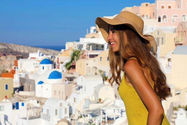 Atrakcyjna opalona kobieta w wiosce oia naprawia się w kapeluszu przed słońcem, patrząc na panoramę miasta z balkonu na wyspie santorini w grecji