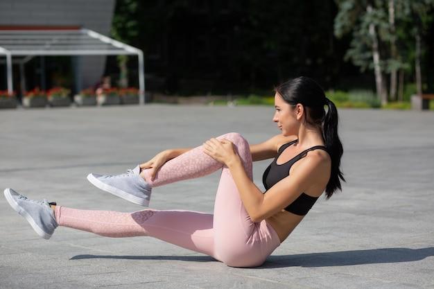 Atrakcyjna opalona sportowa dziewczyna ubrana w sportową odzież, która robi brzuszki w parku