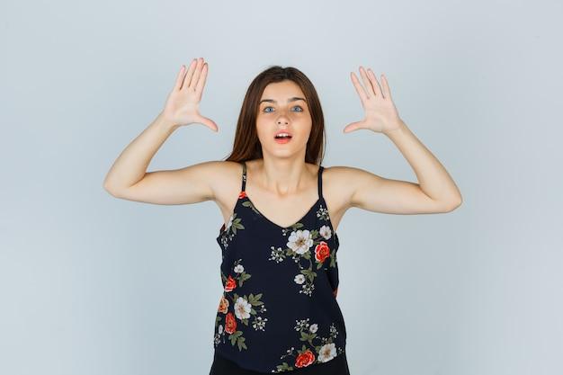 Atrakcyjna pani podnosząc ręce w geście kapitulacji w bluzce i patrząc zdziwiona. przedni widok.