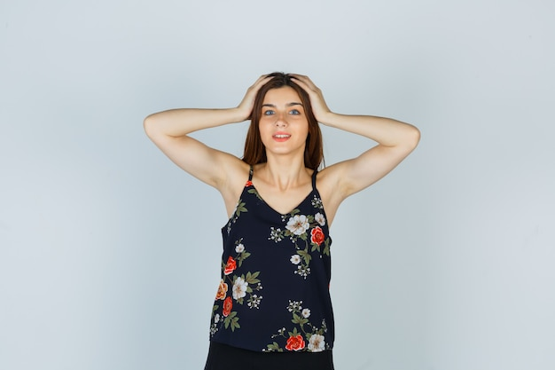 Atrakcyjna pani trzyma ręce na głowie w bluzce i wygląda na zdziwioną, widok z przodu.