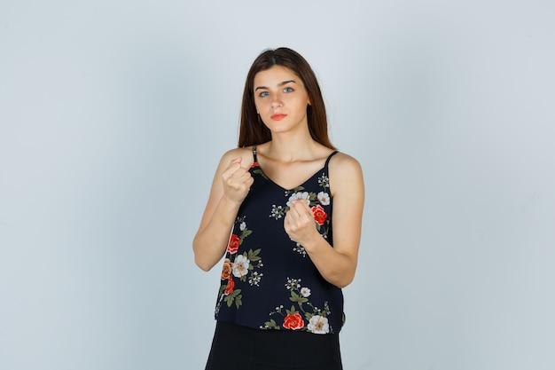 Atrakcyjna pani trzymająca zaciśnięte pięści w bluzce i wyglądająca na złą. przedni widok.