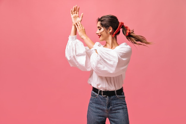 Atrakcyjna pani w białej bluzce, klaszcząca na różowym tle. piękna pani z czerwonym bandażem na włosach i jasną szminką w pozach bluzki.