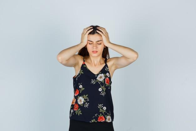 Atrakcyjna pani w bluzce trzymając się za ręce na głowie i patrząc w żałobie, widok z przodu.