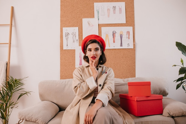 Atrakcyjna pani w czerwonym berecie i beżowym okopie siedzi na kanapie. stylowa dziewczyna o ciemnych włosach w jasny kapelusz i kolczyki pozuje na aparat w pobliżu pudełek.