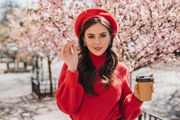 Atrakcyjna pani w czerwonym swetrze idzie aleją z sakurą i pije kawę. piękna kobieta w berecie, uśmiechając się i ciesząc się herbatą poza
