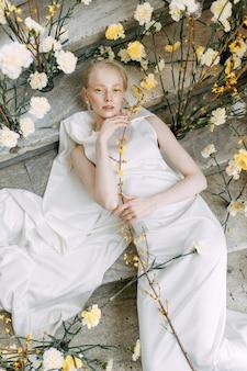 Atrakcyjna panna młoda na kamiennych schodach w europejskim stylu modna żółta florystyka na wesele