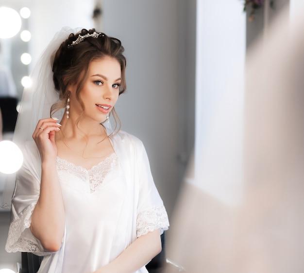 Atrakcyjna panna młoda patrzy na siebie w lustrze