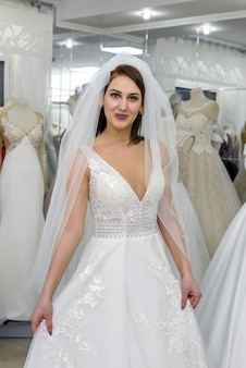 Atrakcyjna panna młoda uśmiecha się w salonie ślubnym