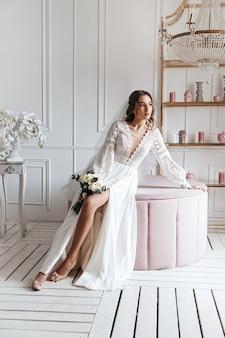 Atrakcyjna panna młoda w pięknej sukni ślubnej boho z bukietem w jasnym pokoju.