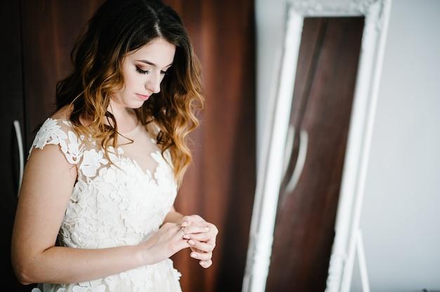 Atrakcyjna panna młoda w sukni ślubnej noszenia i koryguje złoty pierścionek zaręczynowy ślub. przygotowania panny młodej. poranek weselny.