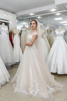 Atrakcyjna panna młoda wybiera suknię ślubną w salonie ślubnym