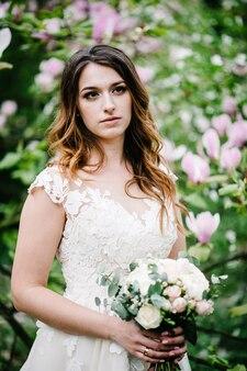 Atrakcyjna panna młoda z bukietem ślubnym stojąc na tle fioletowych kwiatów magnolii i zieleni. natura. na dworze. patrząc na boki. górna połowa długości.