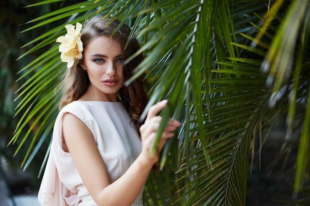 Atrakcyjna panna młoda z długimi kręconymi włosami w sukni ślubnej na tle zielonych liści, fotografia ślubna, portret.