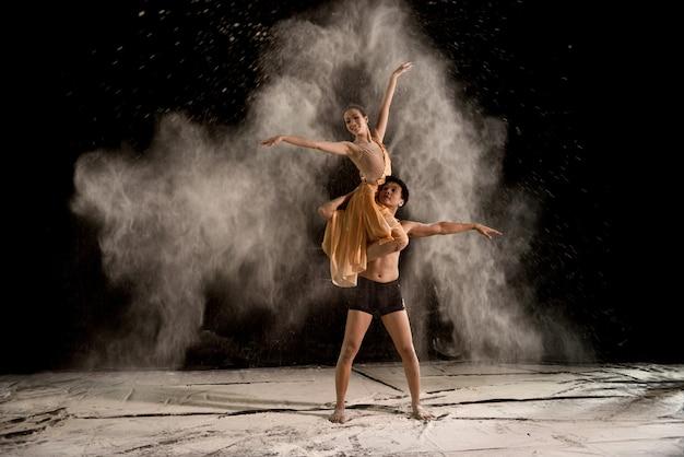 Atrakcyjna para baletnica z białym proszkiem w powietrzu