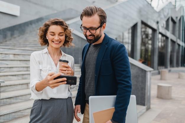 Atrakcyjna para mężczyzny i kobiety w centrum miasta, trzymających telefon i patrzących