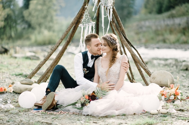 Atrakcyjna para nowożeńcy siedzą na kamieniach