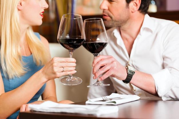 Atrakcyjna para pije czerwone wino w restauracji lub barze