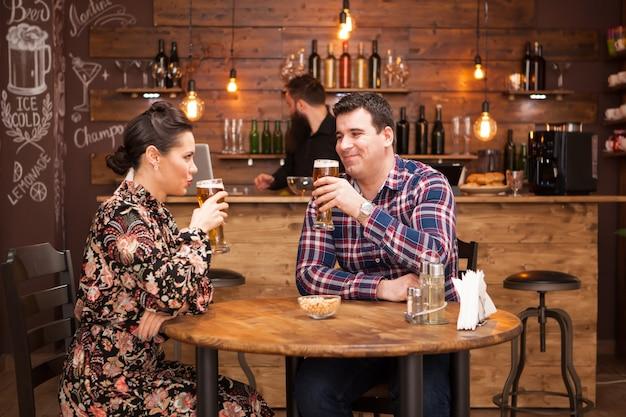 Atrakcyjna para pije piwo w pięknym pubie hipster. szczęśliwa para.
