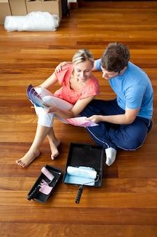 Atrakcyjna para siedzi na podłodze wybierając kolory
